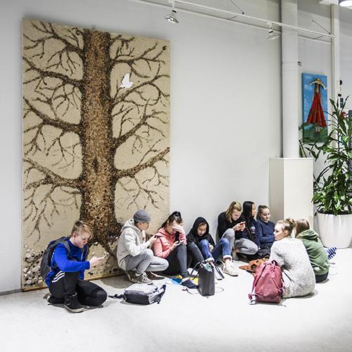 Kuvassa on joukko oppilaita koulun aulassa välitunnilla. Istuvien oppilaiden taustalla on oppilaiden tekemä suuri puuta kuvaava taideteos.