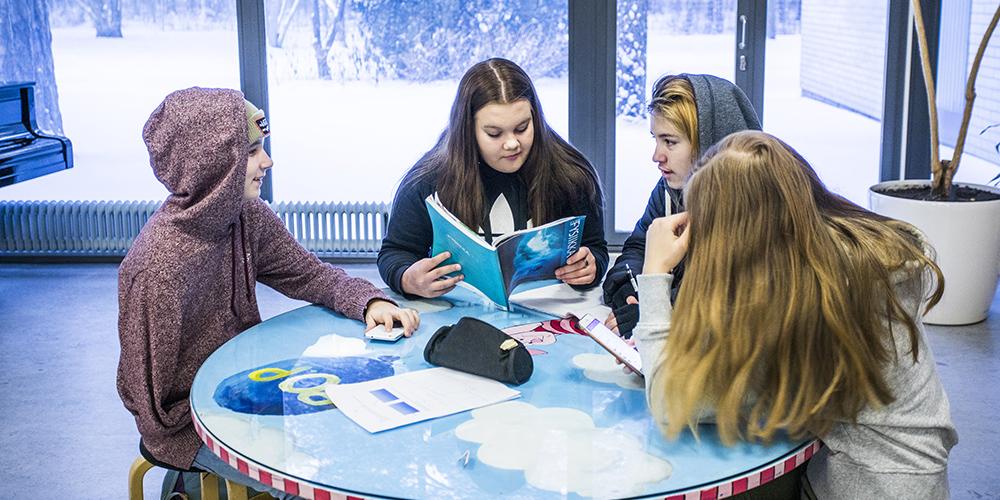 Kuvassa on neljä oppilasta pöydän ääressä koulun aulassa välitunnilla. Taustalla on suuri ikkuna, josta näkyy talvinen metsikkö.