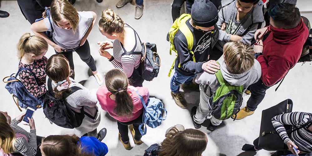 Kuvassa on ylhäältä otettu kuva yläkoulun oppilaista, jotaka juttelevat toisilleen pienissä ryhmissä reput selässään.