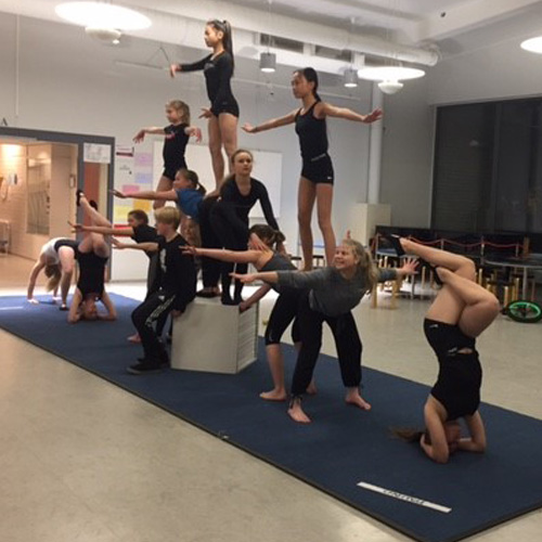Tusinan verran oppilaita ovat tekevät sirkus-harjoituksia ja tasapainoilevat erilaisissa asennoissa.