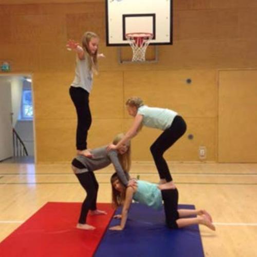 Neljä tyttöä tekevät sirkus-harjoituksia ja ovat asettumassa pyramidi-muodostelmaan.