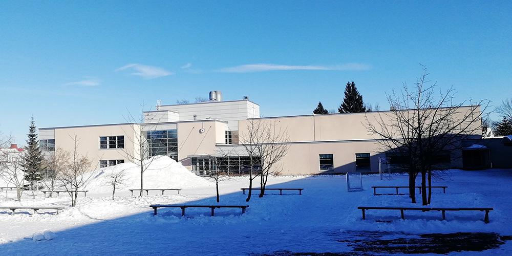 Talvinen ja luminen kirkaan päivän kuva Norssin pihasta, jossa näkyy taustalla vaalea kaksikerroksinen koulun H-siipi.