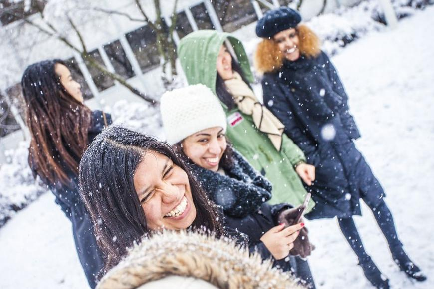 An international student group playing in snow.
