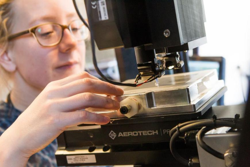 A researcher working on a microscope.