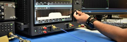 Measurement of a test RF board with Keysight real-time oscilloscope showing a center frequency of 28 GHz. A hand is adjusting one knob to fine tune the visualization.