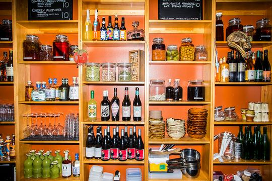 A restaurant's shelf containing bottles and jars.