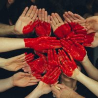 Kädet, joissa maalia ja näistä muodostuu sydän.