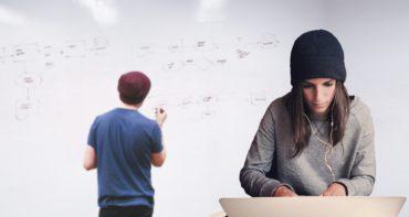 Etualalla pipopäinen nainen kuulokkeet korvilla, katsoo tietokoneen näyttöä. Taka-alalla pipopäinen nuori mies kirjoittaa valkotaululle.