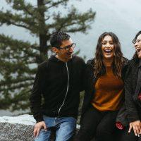 Mies ja kaksi naista istuvat muurilla takanaan sumuinen maisema ja nauravat.